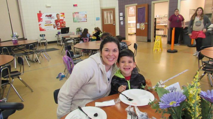 Mom and Son Smiling for Camera while Sitting at Cafeteria Table